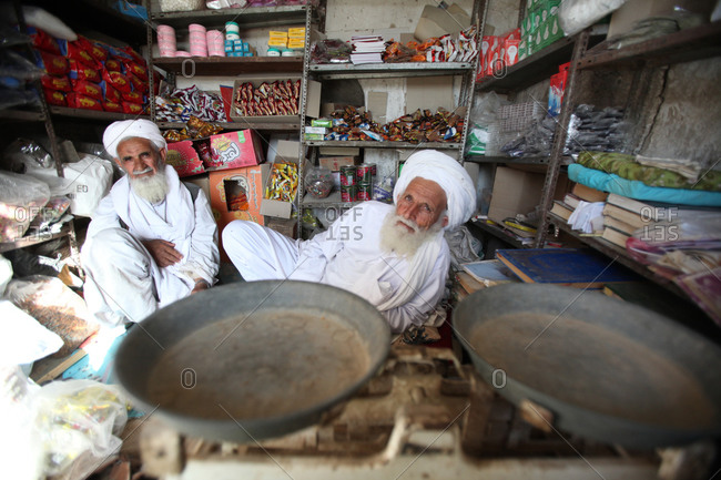 Zabol, Iran - May 1, 2014: Two old men in their store wearing traditional clothes