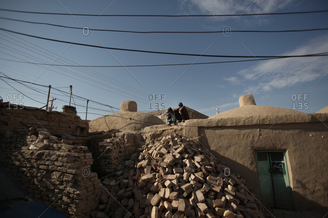 Zabol, Iran - May 1, 2014: Two men sitting on a roof of a house in Kabul