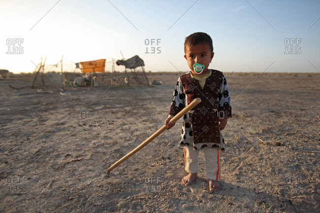 A little girl holding a wood stick in her hand