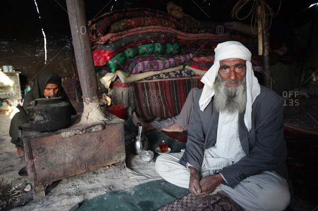 An old man and his wife living in a tent in Iran