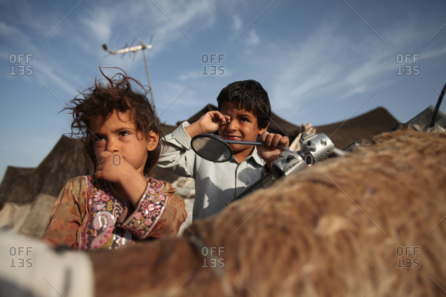 Two kids in Iran desert outside a tent