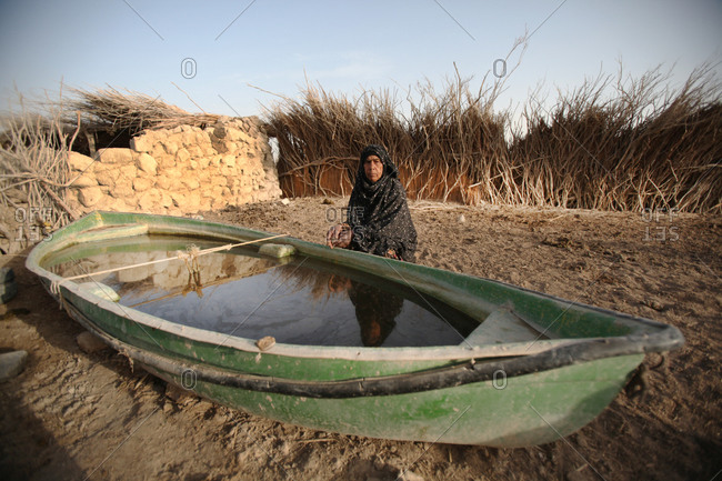 Iranian woman sitting next to a boat filled with water in a village in south Iran