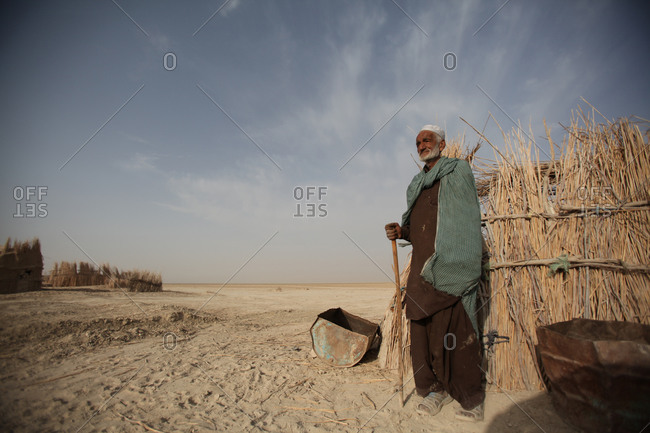 Iranian man holding a stick standing in a village in south Iran