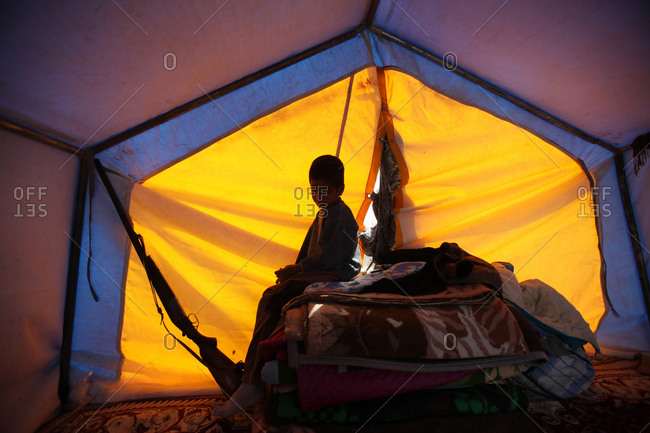 A kid sitting in a dark tent in Iran