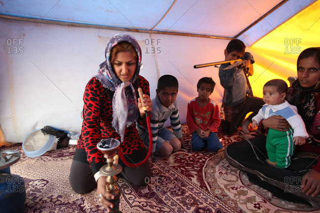 Zabol, Iran - May 4, 2014: An Iranian family sitting in a tent smoking hookah while a kid plays with a gun