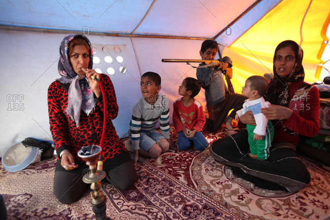 Zabol, Iran - May 4, 2014: An Iranian woman smoking hookah in a tent wile a kid plays with a gun