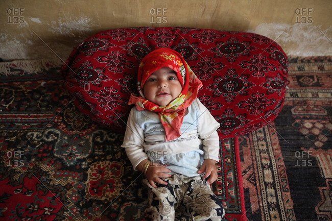 Small Iranian child laying on a rug