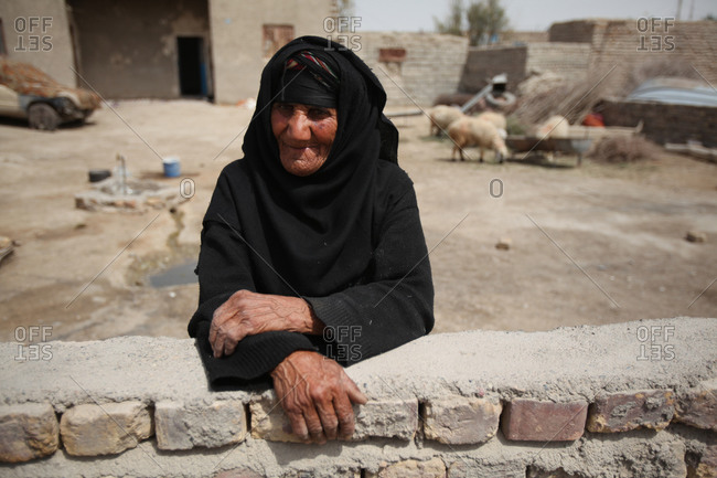 Elderly woman standing outside in a village
