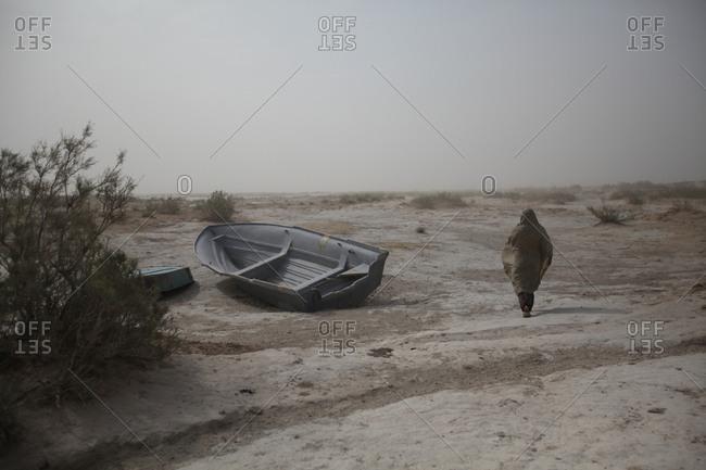 Zabol, Iran - May 2, 2014: Woman walking in the desert in south Iran