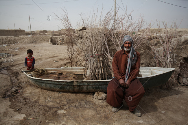 Zabol, Iran - May 2, 2014: Elderly man and a child sitting on a boat in a village in south Iran