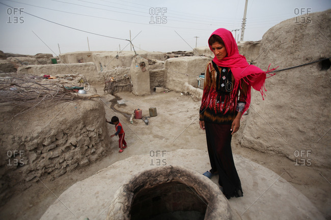 Zabol, Iran - April 8, 2014: Woman looking at a traditional oven in the ground