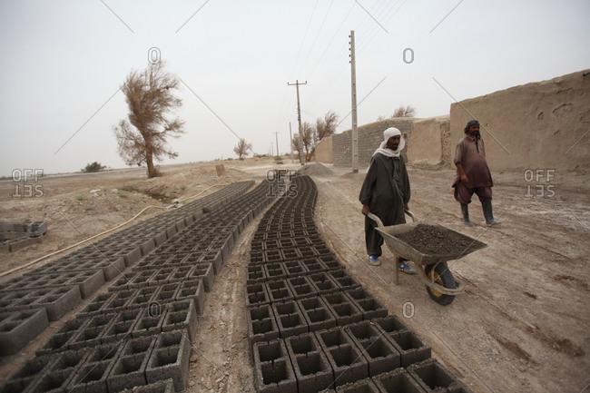Zabol, Iran - May 2, 2014: Workers walking with a wheelbarrow in a village in south Iran