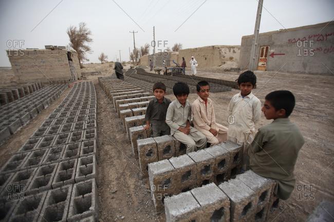 Zabol, Iran - May 2, 2014: Kids sitting on bricks in south Iran village