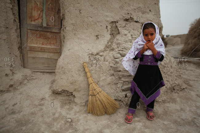 Little girl standing next to a broom in a village