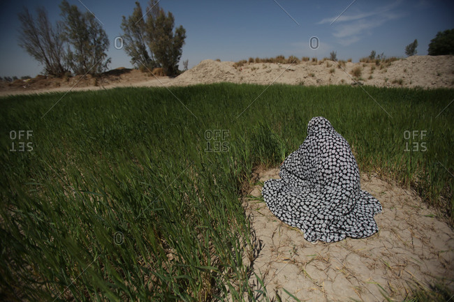 Iranian woman sitting on dry ground surrounded by tall grass