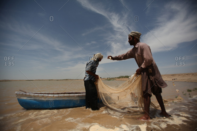 Zabol, Iran - April 9, 2014: Fishermen preparing their net in a lake in south of Iran