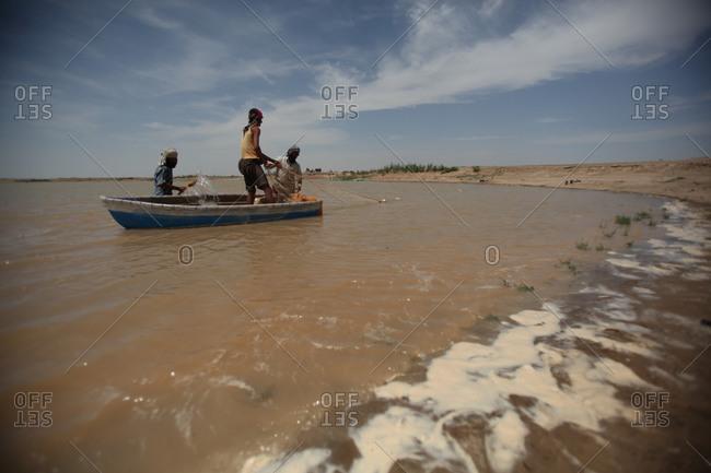Zabol, Iran - April 9, 2014: Fishermen in a little boat in a lake in south Iran