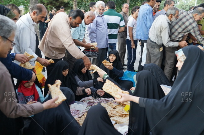 Tehran, Iran - October 10, 2015: A family of martyrs feeding people in the cemetery