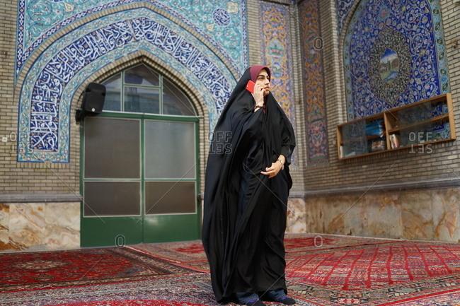 An Iranian girl talking on her phone at bazaar