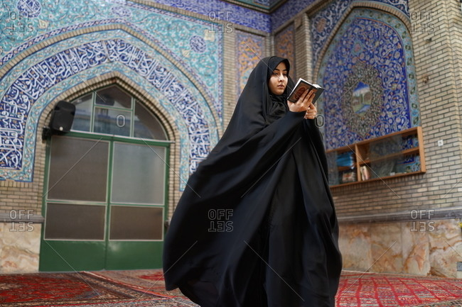 An Iranian girl reading Quran in a mosque in Tehran