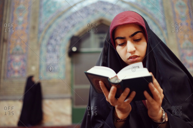 Iranian girl reading Quran in a mosque