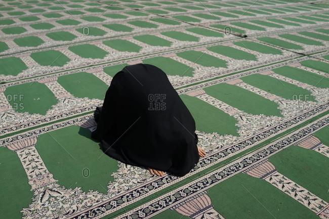 An Iranian girl praying at a mosque