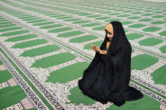 An Iranian girl praying in a mosque by herself