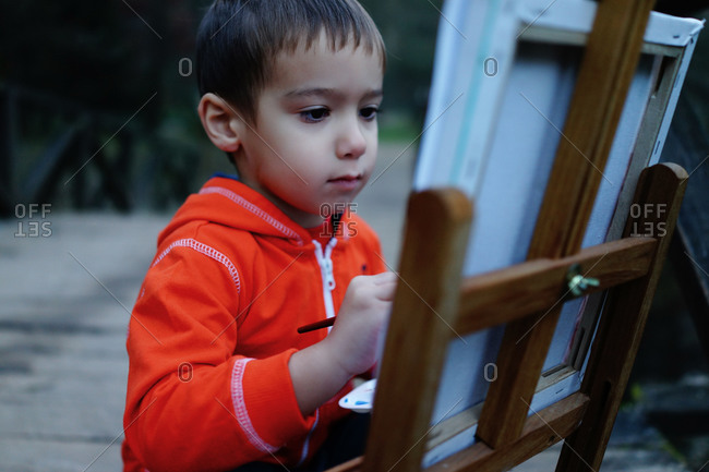 Young boy painting on a canvas outside