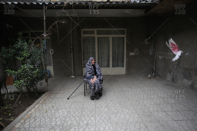 Mother of martyr sitting on a chair looking at a flying bird