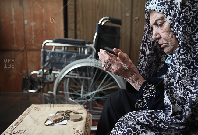 An elderly woman praying at home