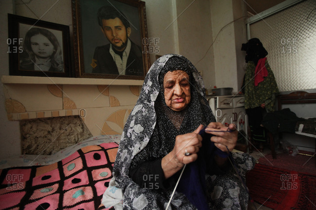Tehran, Iran - January 4, 2015: Mother of martyr sitting on a bed while knitting