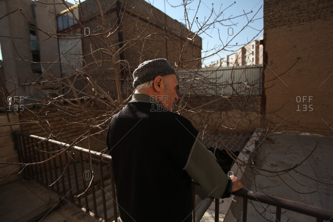 Elderly man standing outside looking at a yard