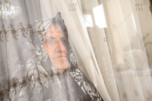 Mother of martyr looking out of a window