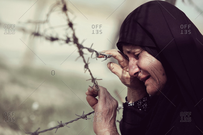 Elderly Iranian woman crying next to barbed wire