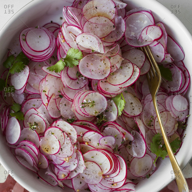 Overhead view of thinly sliced radish salad