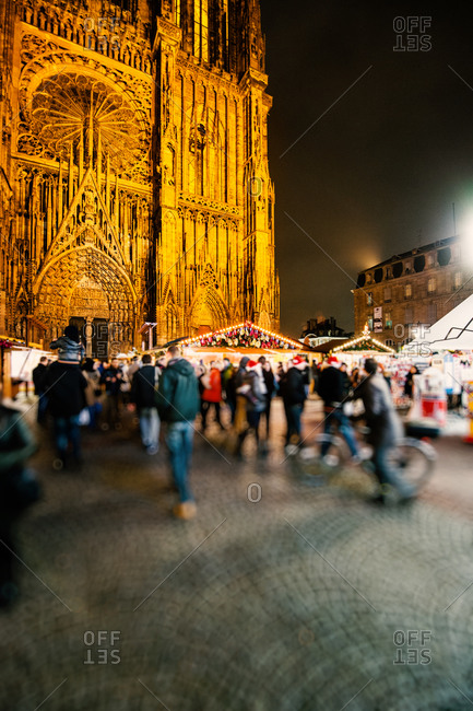 Shoppers at the Christmas market in the Place de la Cathedrale with Notre Dame Cathedral in Strasbourg, France