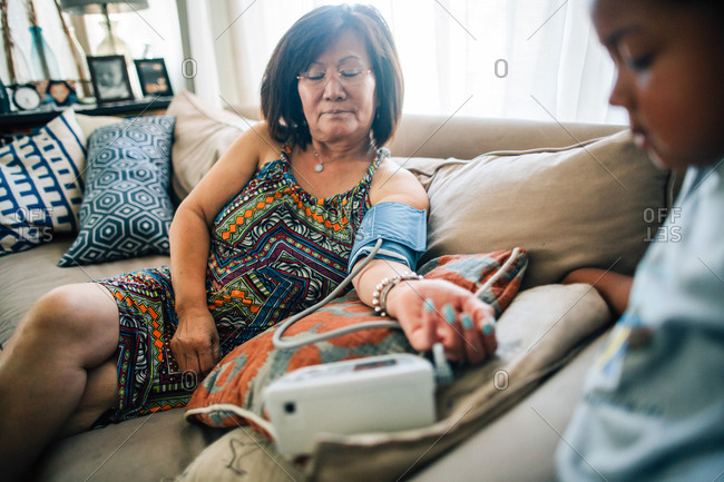 Woman using home blood pressure cuff on sofa