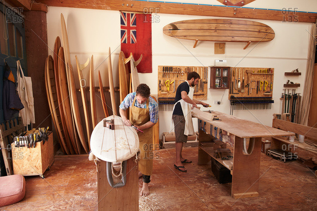 Two men working on wooden surf boards in a shop
