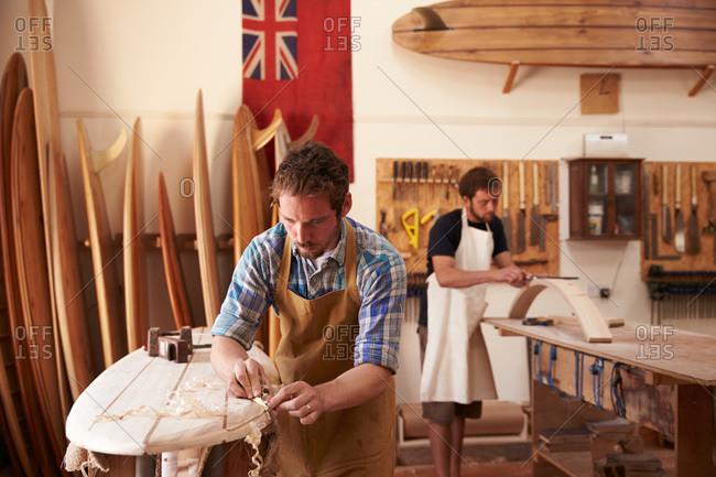 Craftsmen working on wooden surf boards in a shop