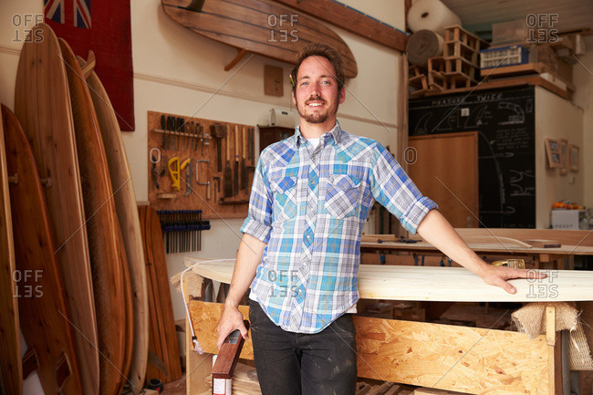 Portrait of a craftsman standing by a surfboard in his shop