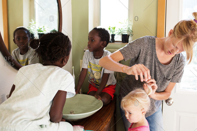 Mother styling her daughter's hair with her three children in the bathroom