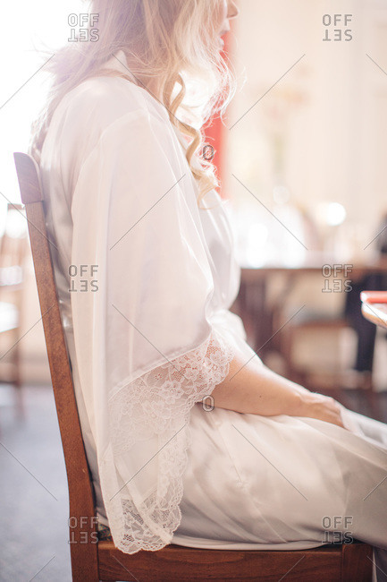 Blond woman in lace trimmed bathrobe sitting in wooden chair