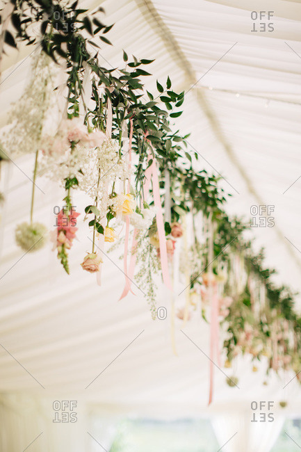 Garland of fresh flowers decorating tent for wedding reception