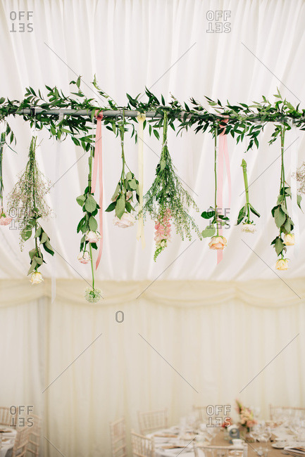 Garland of fresh flowers handing from tent pole for wedding reception