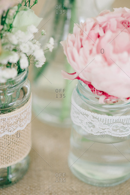 Flower arrangements in glass jars at wedding reception
