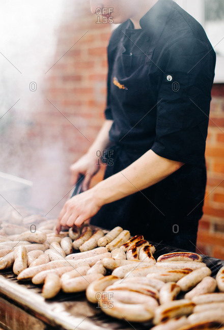 Chef grilling sausages at outdoor grill for banquet
