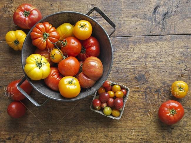 Overhead view of pail and pint of heirloom tomatoes