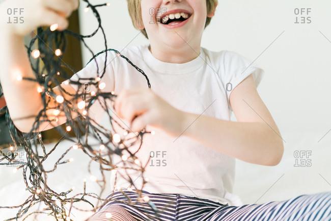 Little boy holding tangled string lights