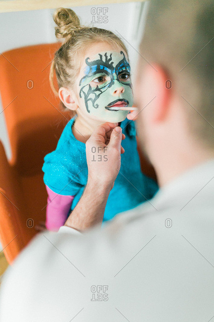 Man painting his daughter\'s face for Halloween