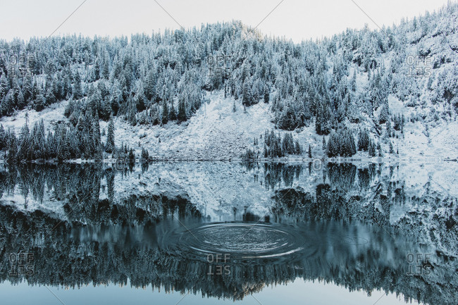 Ripples in water at lake reflecting snowy mountains in Washington